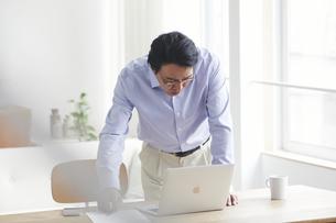 ノートパソコンを見ながら仕事をする男性の写真素材 [FYI04885325]