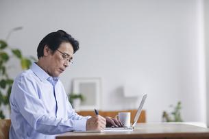 ノートパソコンを見ながら仕事をする男性の写真素材 [FYI04885326]