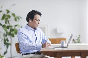 ノートパソコンを見ながら仕事をする男性の写真素材 [FYI04885329]