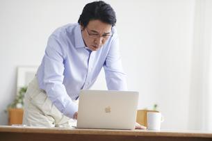 ノートパソコンを見ながら仕事をする男性の写真素材 [FYI04885332]