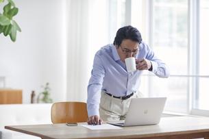 ノートパソコンを見ながら仕事をする男性の写真素材 [FYI04885334]