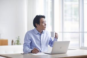ノートパソコンを見ながら仕事をする男性の写真素材 [FYI04885336]