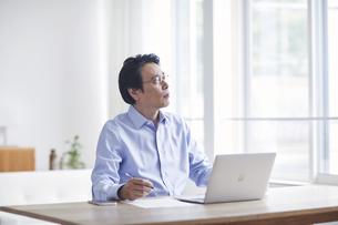 ノートパソコンを見ながら仕事をする男性の写真素材 [FYI04885338]