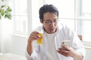 ビールを飲みながらスマホを見る男性の写真素材 [FYI04885339]