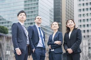 並んでビル群を見上げるビジネスチームの写真素材 [FYI04885417]