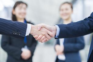 握手シーンと、見守るビジネスウーマンの写真素材 [FYI04885420]