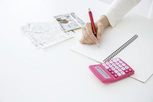 電卓,小銭,レシートを横に置きペンでノートに記入する女性の手のクローズアップの写真素材 [FYI04885561]