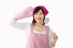 白背景の前でお玉を手にミトンで敬礼する若い女性。元気に明るく料理をする女性イメージの写真素材 [FYI04885563]