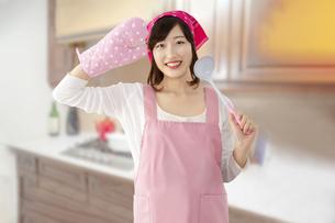 キッチンを背景にお玉を手にミトンで敬礼する若い女性。元気に明るく料理をする女性イメージの写真素材 [FYI04885567]