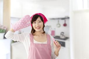 キッチンを背景にお玉を手にミトンで敬礼する若い女性。元気に明るく料理をする女性イメージの写真素材 [FYI04885574]