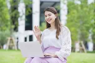 屋外でノートパソコンを操作する女性の写真素材 [FYI04887479]