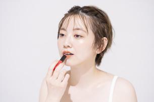 口紅を塗るアジア人の若い女性の写真素材 [FYI04887517]