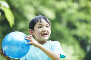 屋外でボールを持って遊ぶ男の子の写真素材 [FYI04889066]