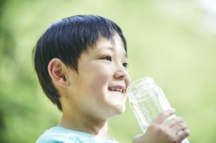 屋外でエコボトルの水を飲む男の子の写真素材 [FYI04889077]