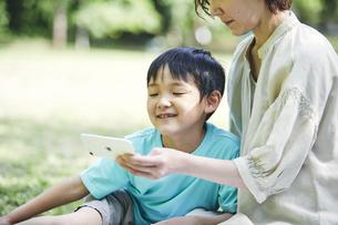 屋外でスマホを見る親子の写真素材 [FYI04889083]