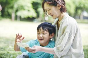屋外でスマホを見る親子の写真素材 [FYI04889089]