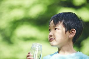 屋外でエコボトルの水を飲む男の子の写真素材 [FYI04889091]