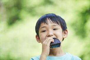 屋外でおにぎりを食べる男の子の写真素材 [FYI04889094]