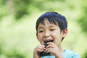 屋外でおにぎりを食べる男の子の写真素材 [FYI04889097]