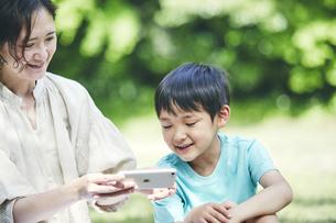 屋外でスマホを見る親子の写真素材 [FYI04889098]