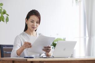ノートパソコンを使い部屋で仕事をする女性の写真素材 [FYI04889387]