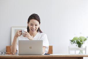 ノートパソコンを使い部屋で仕事をする女性の写真素材 [FYI04889389]