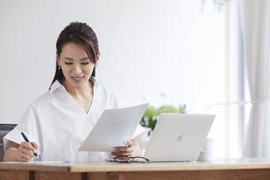 ノートパソコンを使い部屋で仕事をする女性の写真素材 [FYI04889391]