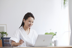 ノートパソコンを使い部屋で仕事をする女性の写真素材 [FYI04889392]