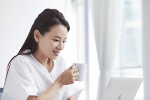 ノートパソコンを使い部屋で仕事をする女性の写真素材 [FYI04889393]