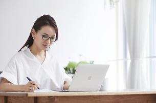 ノートパソコンを使い部屋で仕事をする女性の写真素材 [FYI04889394]