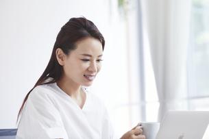 ノートパソコンを使い部屋で仕事をする女性の写真素材 [FYI04889397]