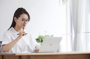 ノートパソコンを使い部屋で仕事をする女性の写真素材 [FYI04889399]
