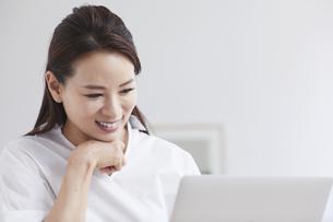 ノートパソコンを使い部屋で仕事をする女性の写真素材 [FYI04889400]