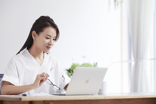 ノートパソコンを使い部屋で仕事をする女性の写真素材 [FYI04889408]