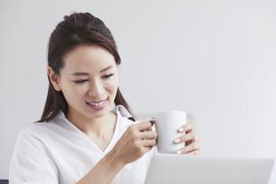 ノートパソコンを使い部屋で仕事をする女性の写真素材 [FYI04889409]