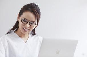 ノートパソコンを使い部屋で仕事をする女性の写真素材 [FYI04889414]