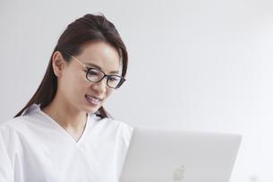 ノートパソコンを使い部屋で仕事をする女性の写真素材 [FYI04889417]