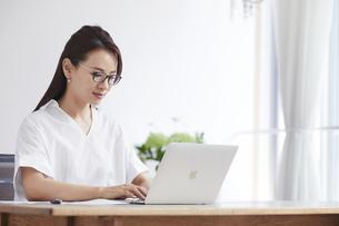 ノートパソコンを使い部屋で仕事をする女性の写真素材 [FYI04889418]