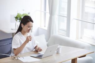 ノートパソコンを使い部屋で仕事をする女性の写真素材 [FYI04889420]
