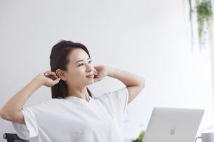 ノートパソコンを使い部屋で仕事をする女性の写真素材 [FYI04889422]