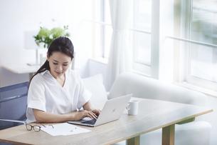 ノートパソコンを使い部屋で仕事をする女性の写真素材 [FYI04889425]
