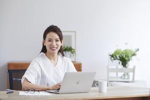 ノートパソコンを使い部屋で仕事をする女性の写真素材 [FYI04889426]