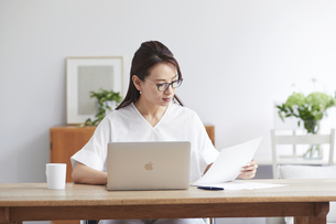 ノートパソコンを使い部屋で仕事をする女性の写真素材 [FYI04889428]