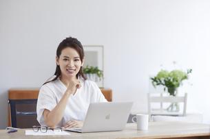 ノートパソコンを使い部屋で仕事をする女性の写真素材 [FYI04889431]