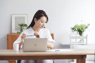 ノートパソコンを使い部屋で仕事をする女性の写真素材 [FYI04889434]