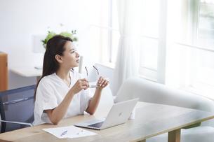 ノートパソコンを使い部屋で仕事をする女性の写真素材 [FYI04889435]