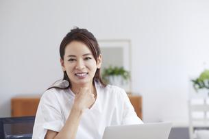 ノートパソコンを使い部屋で仕事をする女性の写真素材 [FYI04889437]