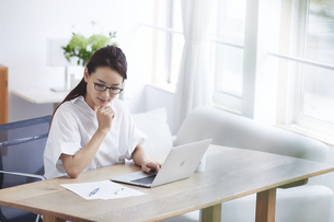 ノートパソコンを使い部屋で仕事をする女性の写真素材 [FYI04889438]