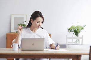 ノートパソコンを使い部屋で仕事をする女性の写真素材 [FYI04889440]