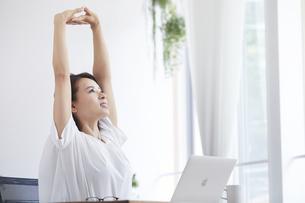 ノートパソコンを使い部屋で仕事をする女性の写真素材 [FYI04889441]